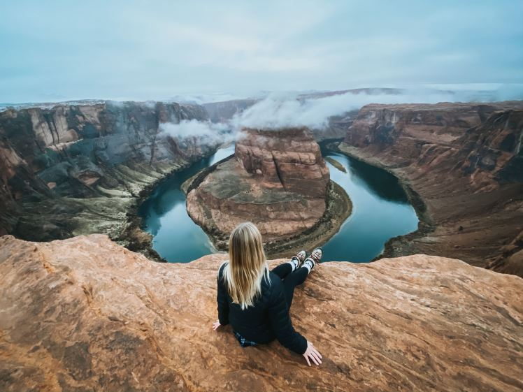 Kay sitting infront of a canyon with a river shaped like a horseshoe