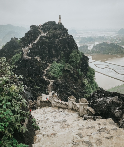 Ancient staircase with uneven steps and a temple at the mountain top