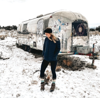 Kay standing in snow outside of an airstream in the Grand Canyon
